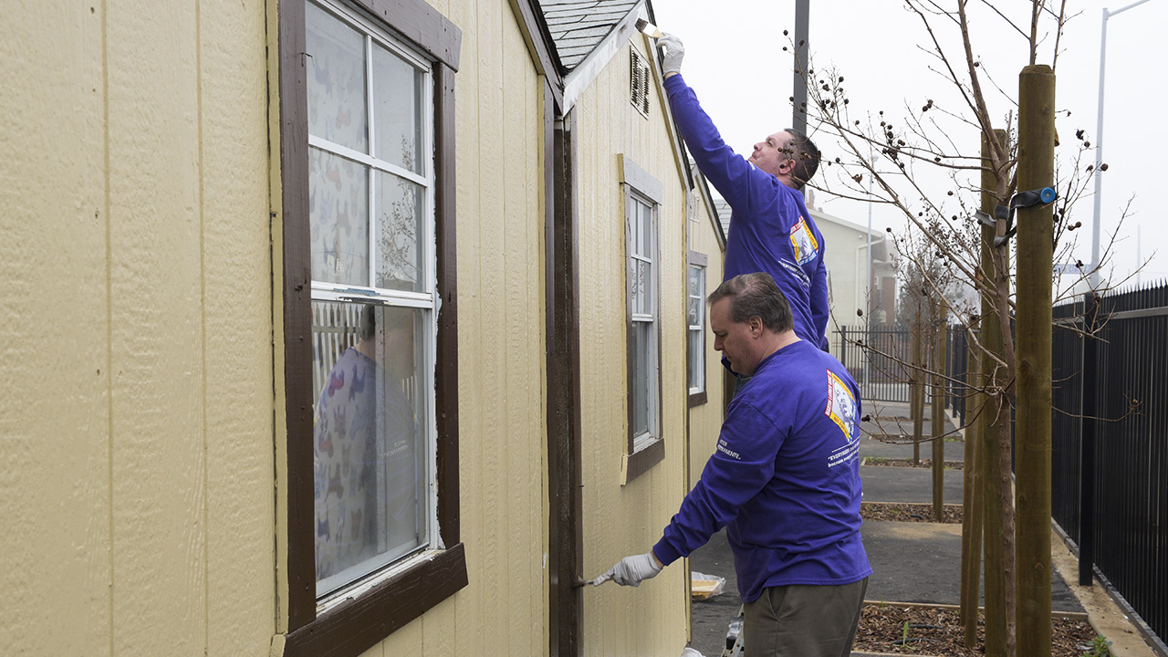 Kaiser volunteers Jason Cascino paints high, while Fred Ford paints low at Poverello House (photo: Randy Reed)