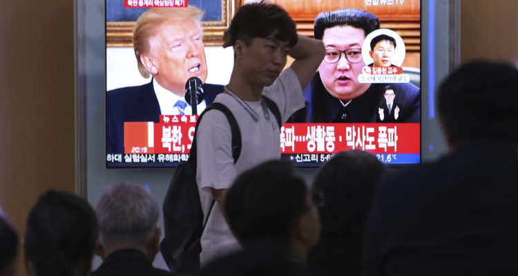 People watch a TV screen showing Donald Trump, left, and Kim Jong Un