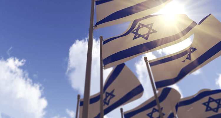 Israel flags against a blue sky with sun shining through