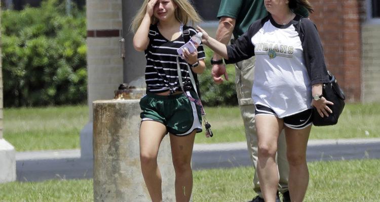 A student, left, reacts after retrieving her belongings inside Santa Fe High School in Santa Fe, Texas.