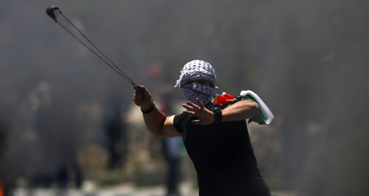 A Palestinian protester hurls a stone during clashes with Israeli forces