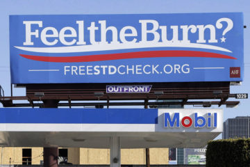 "A billboard above a gas station that reads ""Feel The Burn,"" actually promotes free STD testing."