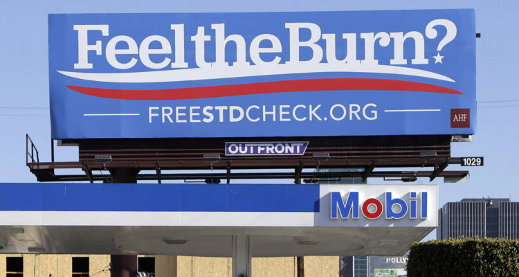 """A billboard above a gas station that reads """"Feel The Burn,"""" actually promotes free STD testing."""