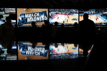 AP picture of people watching coverage of the first round of the NCAA college basketball tournament at the Westgate Superbook sports book in Las Vegas on March 15, 2018.