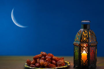 Picture of dates and Ramadan lamp against a silhouette of a sliver of the moon.