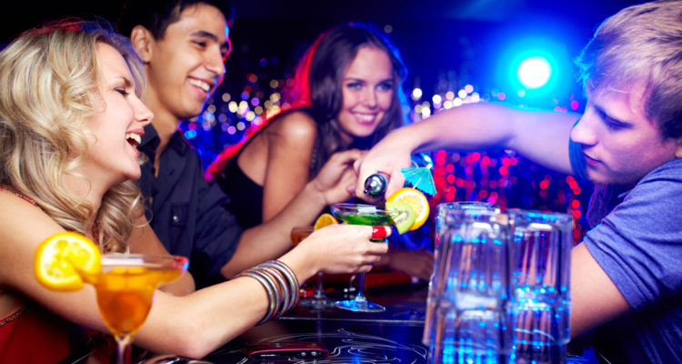 Picture of young adults drinking cocktails at a bar.