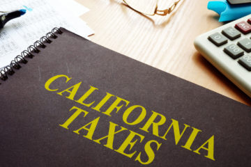 "Picture of a ledger on a desk. The ledger is titled ""California Taxes."""