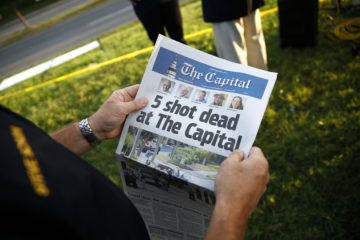 Photo of man reading Capital Gazette one day after a mass shooting at the newspaper
