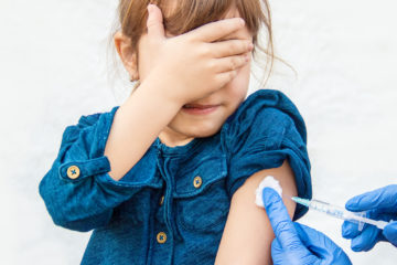 A photo of a young girl covering her eyes while receiving a shot.