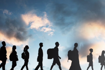 Image of immigrants in silhouette walking with luggage