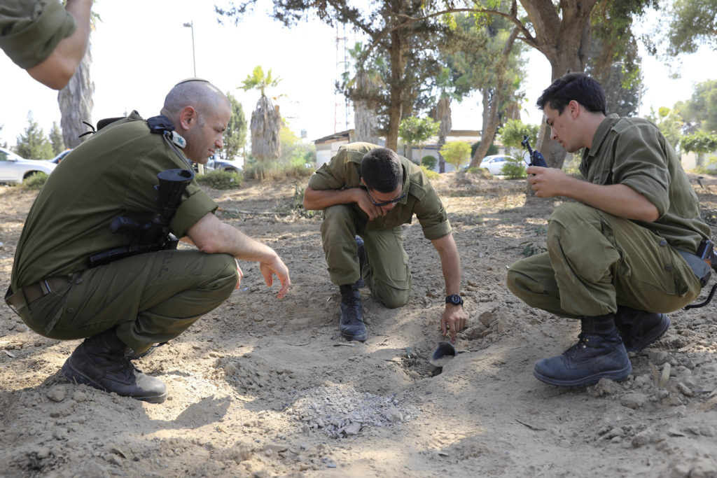 Photo of Israeli soldiers inspecting a missile launched by Hamas.