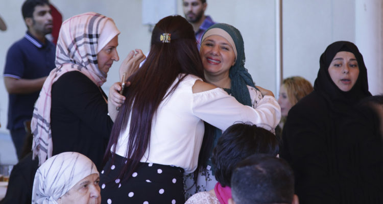 Photo of Muslims hugging at the end of the Ramadan Fast in Fresno, CA.