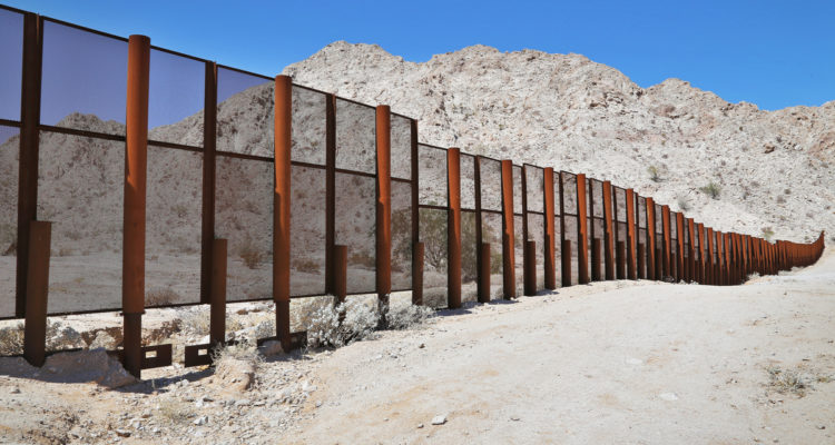 Photo of steel fence protecting the border between Mexico and the United States at the Tinajas Altas Mountains in Arizona.