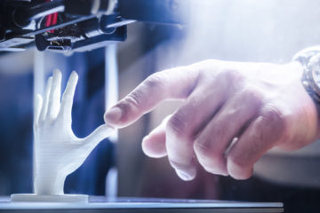 Photo of a 3D printer creating a plastic hand