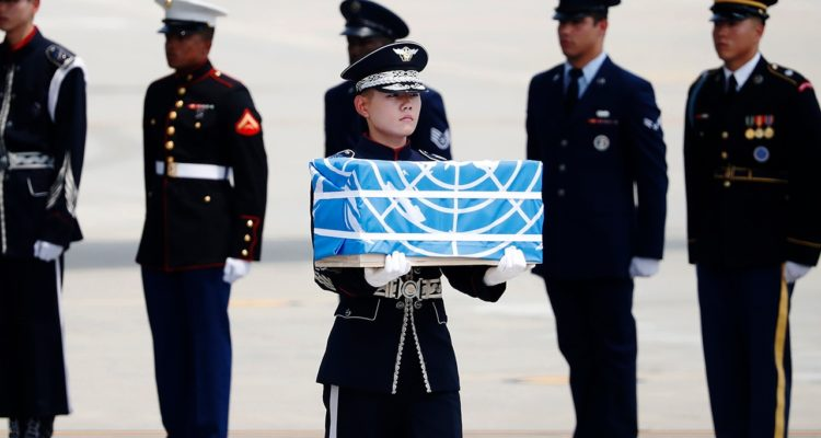 Photo of soldier carrying a casket containing a remain of a US soldier