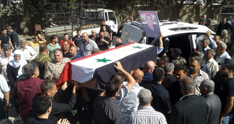 Photo of mourners carrying a coffin after IS attacks in Syria