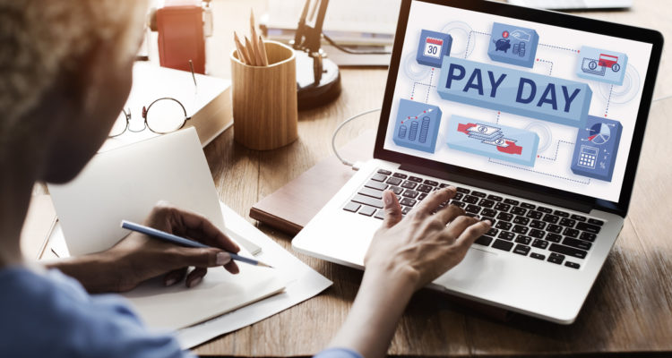 Photo of man paying bills via computer on payday