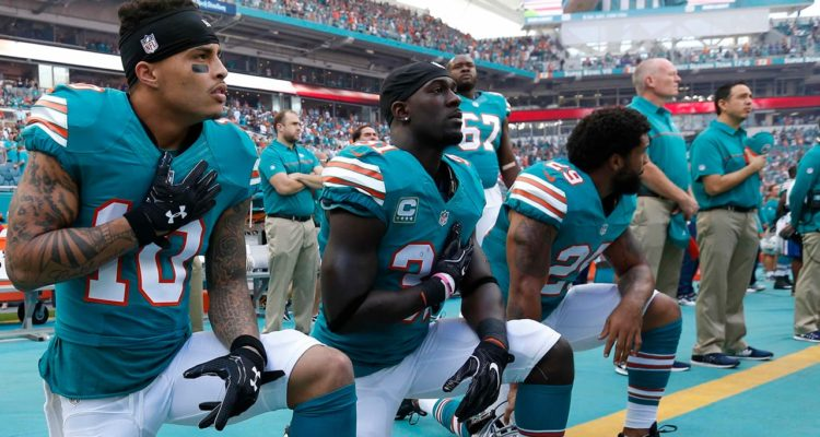 Photo of Miami Dolphins kneeling during the National Anthem before NFL game