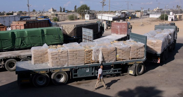Photo of Palestinian worker next to cargo trucks