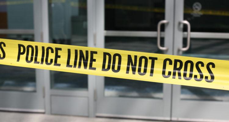 Photo of crime scene tape across plate-glass doors