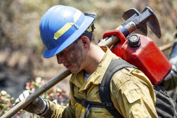 """Photo of a """"hot shot"""" firefighter carrying his gear"""