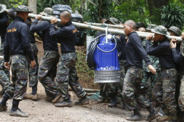 Photo of soldiers carrying a pump to drain Thai cave