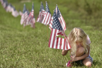 AP photo of a young girl putting American flags into the ground