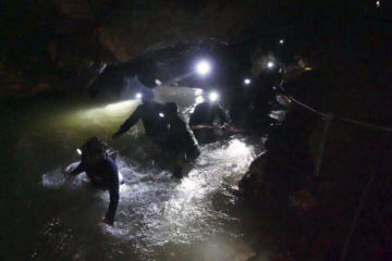 Rescue team in Thailand looking for young soccer players and their coach walk through a cave.