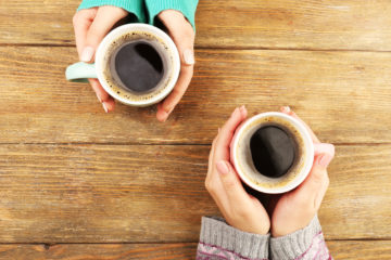 Shutterstock photo of two female hands holding cups of coffee