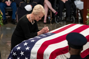 Photo of Cindy McCain leaning over John McCain's casket