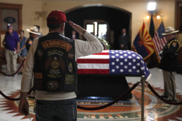 Photo of retired Marine saluting the casket of John McCain