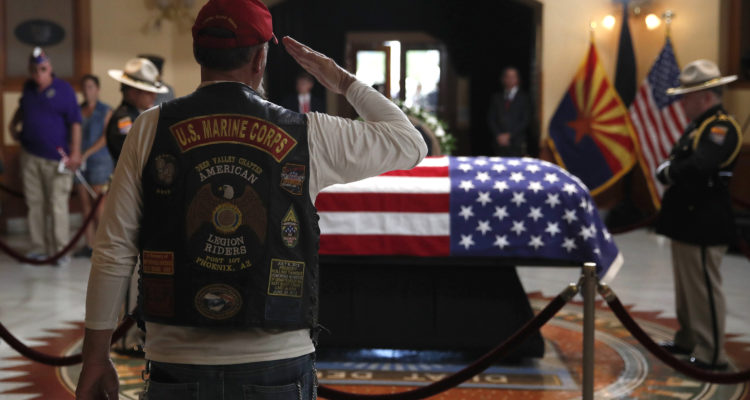 Photo of retired Marine saluting the casket of John McCain
