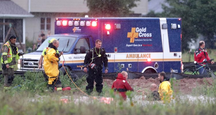 Photo of emergency responders rescuing boy that got sucked into a storm sewer