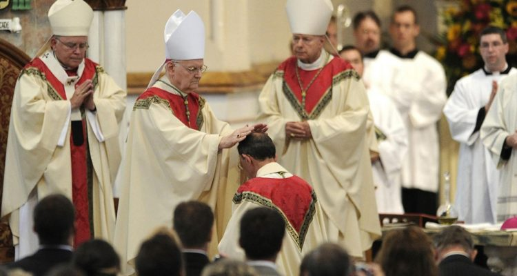Photo of retiring bishop kneeling and praying