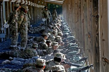 Photo of Army drill sergeants standing over recruits