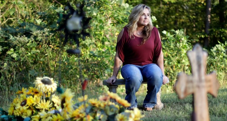 Photo of Heather Melton sitting by the grave of her late husband, Sonny Melton