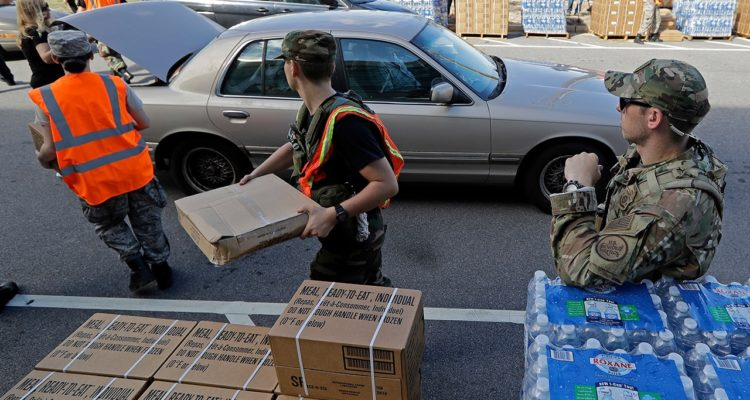 Photo of members of the Civil Air Patrol loading cars with MREs, water and tarps