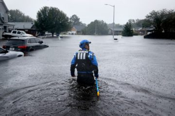 Photo of a member of the North Carolina Task Force search and rescue team wading through flooded neighborhoods