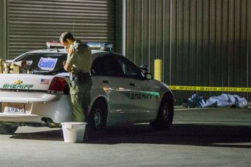Photo of Kern County sheriff's deputy stands near an area where a shooting victim lies