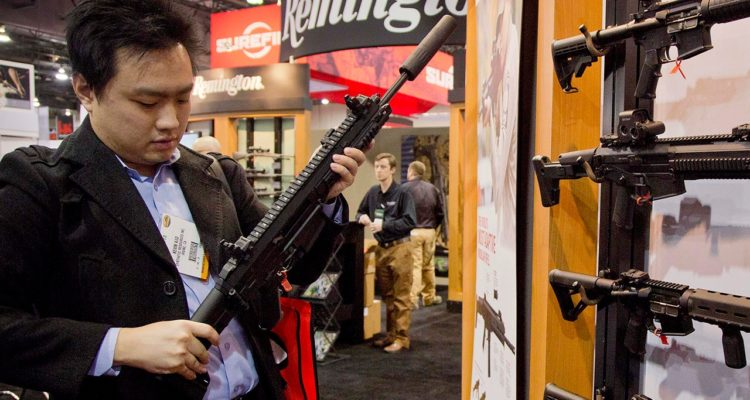 Photo of accessories manufacturer Kevin Kao examining a military grade Remington Adaptive Combat Rifle