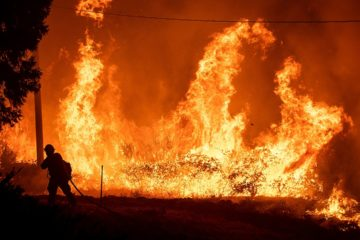 Photo of a firefighter passing through flames while battling Delta Fire