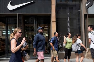 Photo of people passing in front of a Nike store in New York