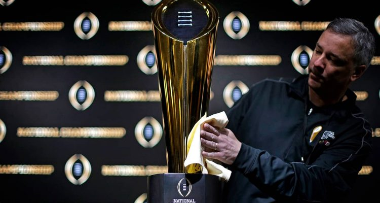 Photo of Charley Green buffing the NCAA college football championship trophy