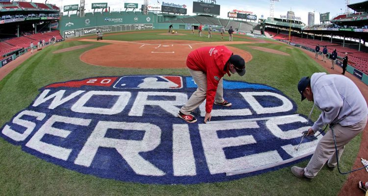 Photo of crew members painting the World Series logo at Fenway Park