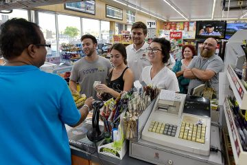 Photo of people lining up at a store to buy lottery tickets