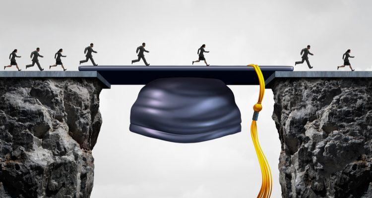 Photo of graduates crossing a gap filled by a graduation mortar cap