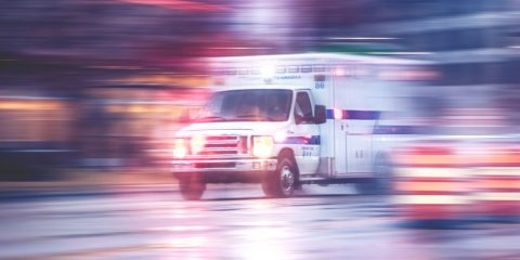 Photo of ambulance racing through city streets on a rainy night