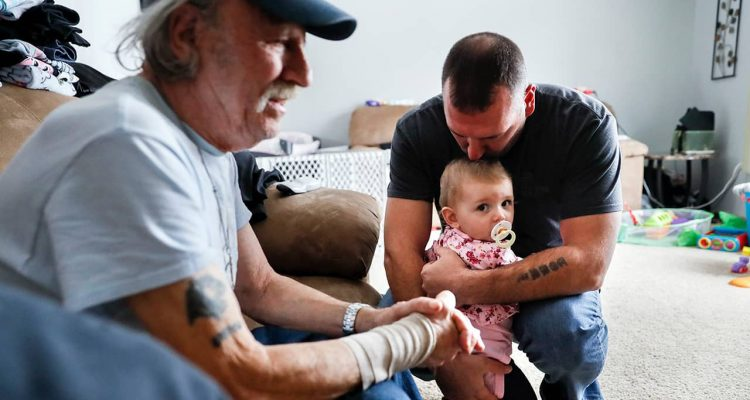 Tom Wolikow, right, holds his daughter Annabella alongside his father John