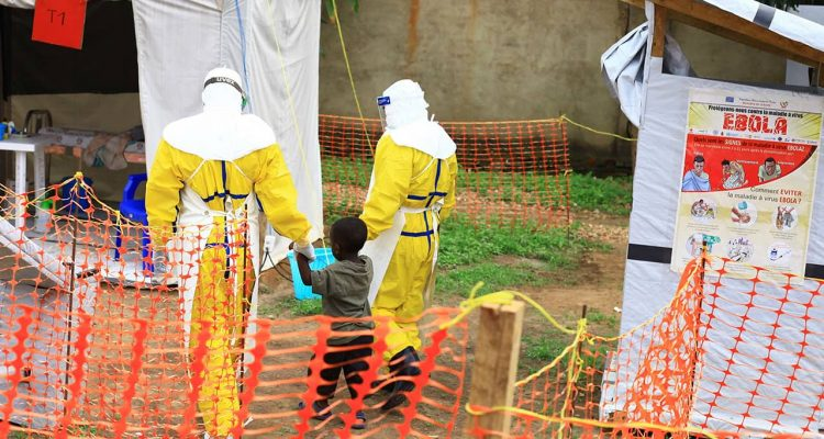 Photo of health workers walking with a boy that has ebola