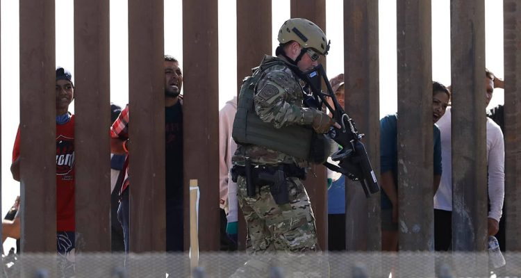 Photo of Border Protection officers walking along a wall at the border between Mexico and the U.S.